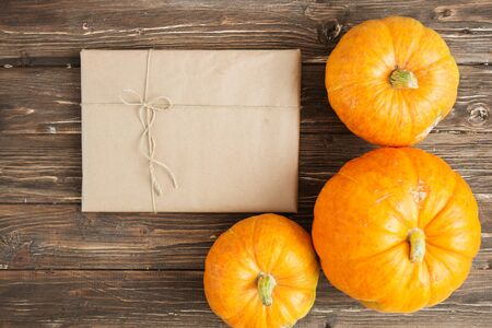 Pumpkin with gift in brown paper package tied up with strings on a grunge wooden backdrop. Thanksgiving and Halloween concept. View from above. Top view. Copy space for text and design 스톡 콘텐츠