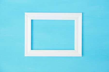 Vintage white mockup, frame on old blue wooden bacground Фото со стока - 129815113