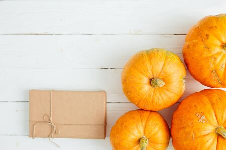 Orange pumpkins with gift in brown paper package tied up with strings on old white wooden background Thanksgiving and Halloween concept. Top view. Copy space for text and design 스톡 콘텐츠