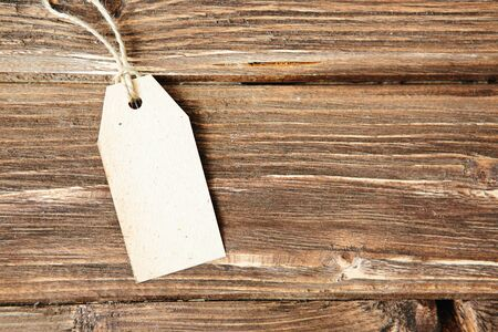 Blank label on wooden background One paper blank tags with rope on wooden background.