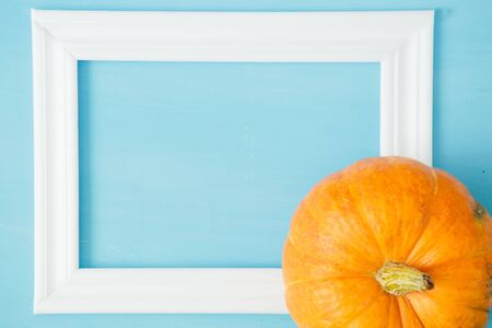 Thanksgiving season still life with orange pumpkins and with white frame for picture over rustic blue wood background Thanksgiving and Halloween concept. Copy space for text and design 스톡 콘텐츠