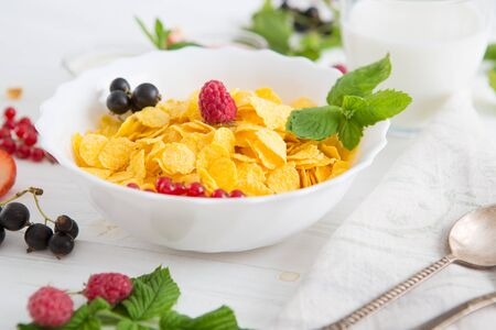 oatmeal with nuts and dried fruits on old white painted wooden table. Perfect breakfast Healthy tasty breakfast cornflakes with strawberries, raspberries, black currants and red currants. 스톡 콘텐츠