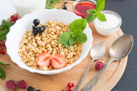 Fresh granola, muesli with yogurt and berries on marble background. Healthy tasty breakfast of muesli with strawberries, raspberries, black currants and red currants.