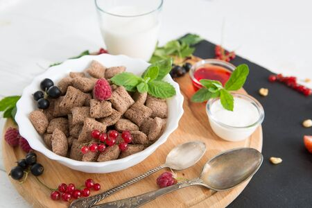 healthy breakfast cereal with fruit on the summer table Healthy tasty breakfast chocolate square pads with strawberries, raspberries, black currants and red currants. 스톡 콘텐츠