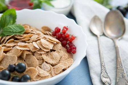 Ingredients tasty healthy breakfast for cooking with milk. Healthy tasty breakfast multigrain wholewheat healthy cereals with strawberries, raspberries, black currants and red currants. 스톡 콘텐츠