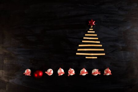 Line of christmas balls and christmas tree from dry sticks on dark wooden background