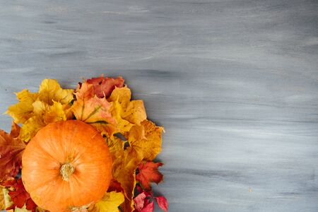 Autumn leaves and pumpkin over old wooden background with copy space Thanksgiving and Halloween concept. View from above. Top view. Copy space for text and design