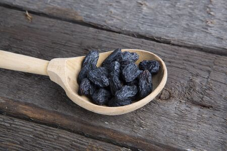 Raisins in a wooden spoon