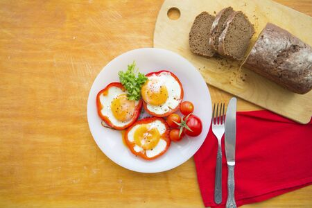 fried eggs in red peppers in a plate close-up. horizontal view from above Banco de Imagens