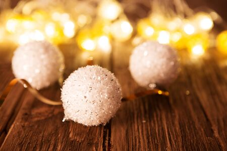 Christmas balls with Christmas lights on dark wooden background