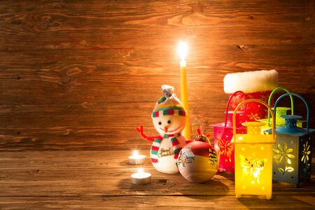 Handmade snowman, lamp with a candle and Christmas decoration on a wooden table background. Archivio Fotografico - 133677824