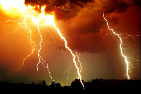 Colpo di fulmine sul cielo nuvoloso scuro. Immagine dai toni arancio, giallo e rosso.