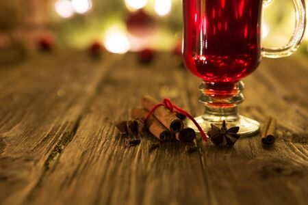Single glass of hot mulled on defocused christmas tree background.