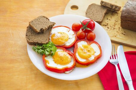 Fried eggs in red peppers. Fried eggs in paprika served on white plate on wooden background Фото со стока