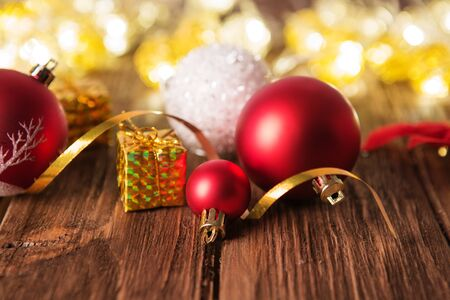 Christmas tree decorations laying on a rustic wooden table against christmas lights