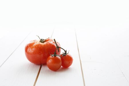 Delicious red tomatoes cherry on a white wood table background. Stock fotó