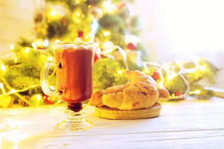 Winter hot chocolate with marshmallows and a croissant on a white wooden table against the background of the Christmas tree. Decorating and christmas tree