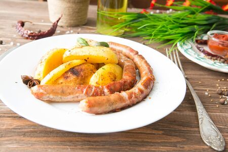 Grilled sausages and mashed potato on a white plate and wooden background Stock Photo