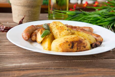 Grilled sausages with herb potatoes and ketchup, tasty summer picnic dish, sausages on skewers a dark wooden background