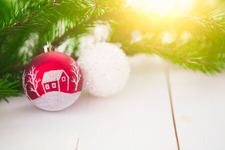 Red and white xmas holiday balls ornament sits among pine or spruce branches on wooden table.