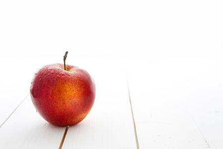 Delicious appetizing beautiful fresh red apple isolated on a white wood table background.