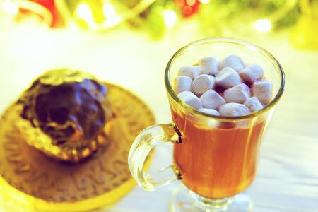 Hot drink with marshmallows on the background of Christmas decorations. Decorating and christmas tree