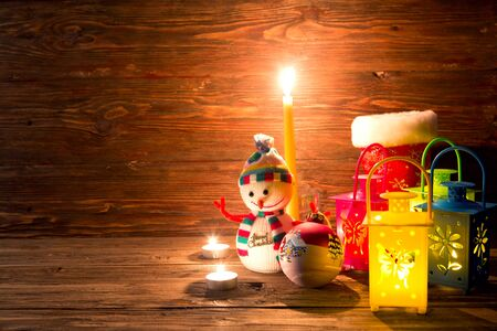 Christmas candle and snowman toy on wooden wall with copy space. Archivio Fotografico - 133679896