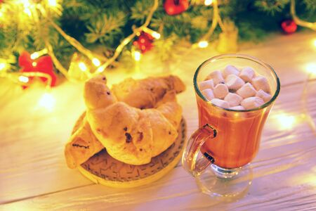 Winter hot chocolate with marshmallows and a croissant on a white wooden table against the background of the Christmas tree. Reklamní fotografie