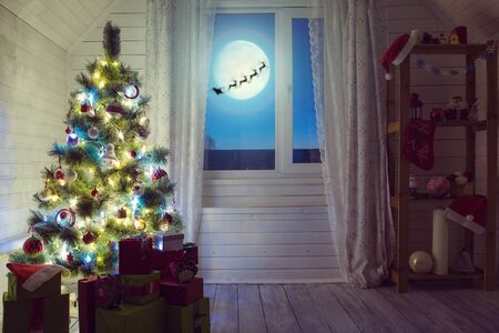 Christmas home room with tree and moon lighting in window.