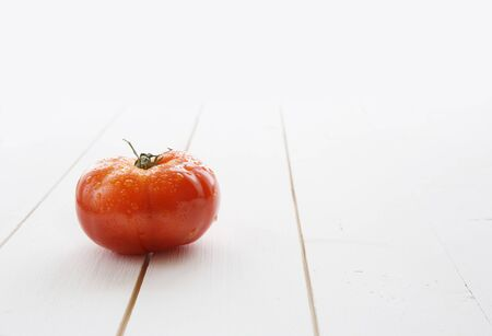 Delicious red tomato on a white wood table background.