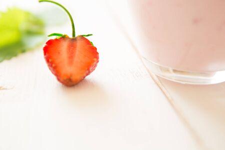 Gros plan aux fraises sur une table en bois rustique avec du yaourt.