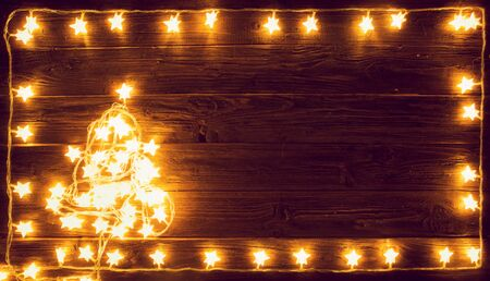 Christmas tree of Christmas lights on a wooden background. Blur christmas lights on wooden planks.