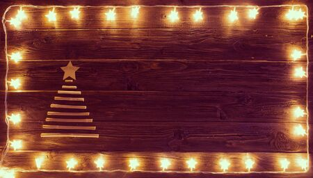Christmas lights with a Christmas tree of dried branches on a wooden background. Blur christmas lights on wooden planks. Reklamní fotografie