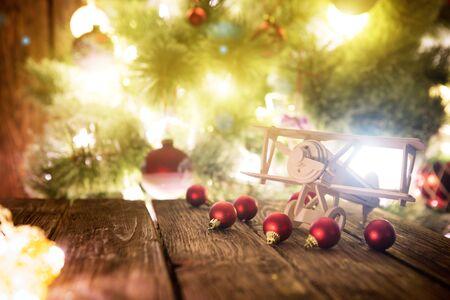Fond de vacances de Noël avec avion en bois et boules rouges de Noël sur le dessus de table en bois au-dessus de la lumière festive de bokeh décorer sur l'arbre de Noël.