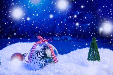 Weihnachtshintergrund mit Weihnachtskugeln auf Schnee über Tannenbaum, Nachthimmel und Mond. Geringe Schärfentiefe. Weihnachten Hintergrund. Märchen. Makro. Künstliche magische verträumte Welt.