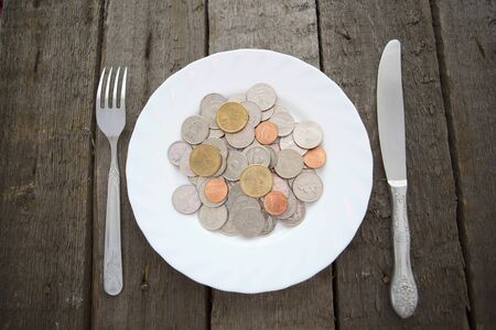 Coins on a plate with fork and knife on wooden table