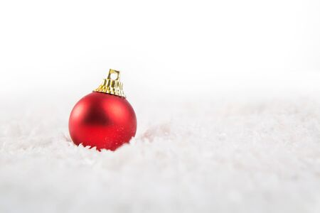 Red christmas ball on snow over white background 写真素材