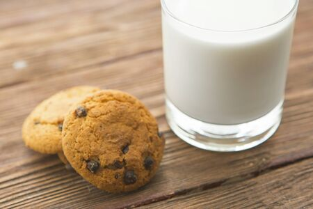 Chocolate chip cookies and a glass of milk on wooden table Stock Photo