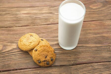 Cookies and glass of milk on wooden table