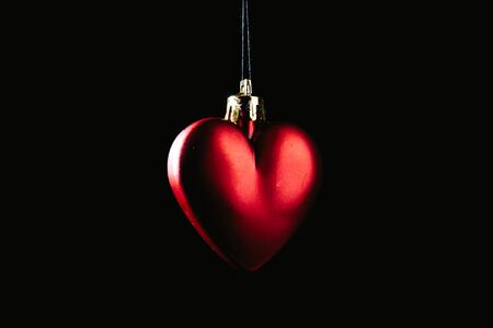 Red Christmas bauble over dark background. Low key photo. Heart shape.