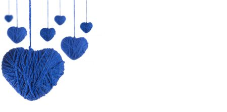 Perspective of hearts made of blue wool yarn on a white background