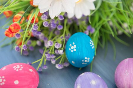 Easter eggs and flowers on a gray wooden planks