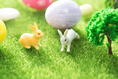 Two rabbit toys with easter eggs on a meadow grass. Yellow easter egg spring meadow with a two rabbit and easter eggs. Fairy tale