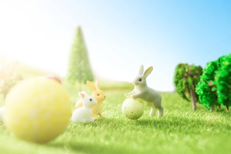 Easter rabbits on a green grass with Easter eggs in Dreamland or fairy world. Stock Photo