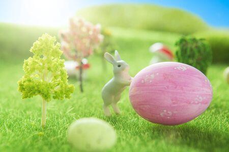 Rabbits near an easter eggs on a green grass field.