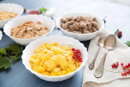 Tazones de varios cereales y leche desde la vista superior Mezcla de cereales para el desayuno: copos de maíz, almohadillas, muesli, copos multicereales y bolas de chocolate Foto de archivo