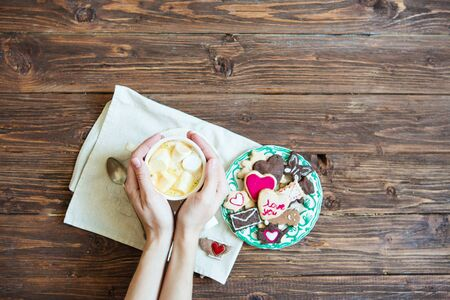 Hand holding a Cup of hot cocoa or chocolate with marshmallows on a wooden background