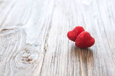 Two red heart on wooden table textured against the bokeh background