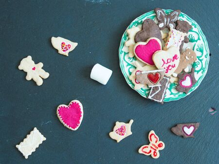 Cookies on black stone background. Valentines day greeting card. Love and holiday concept.