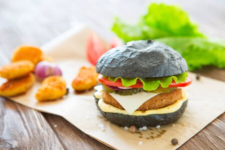 Delicious fast food. One black burger isolated on black background. Above view.